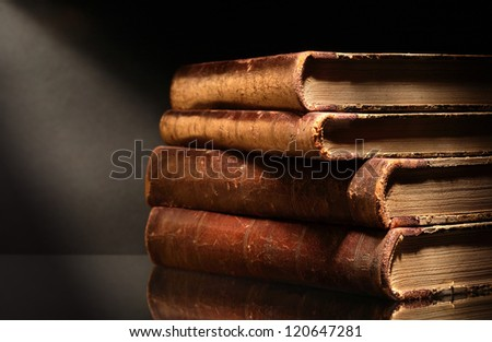 Stack of old books on dark background - stock photo