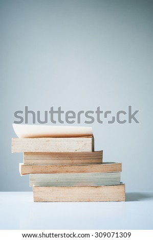 Stack of old books on white table - stock photo