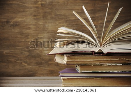 Stack of old books on wooden background. - stock photo