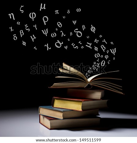 stack of old books, one on top opened with letters flying out, on dark black background - stock photo