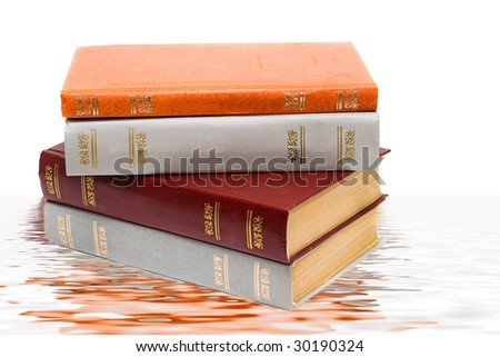 Stack of old books reflected on water and isolated on white - stock photo