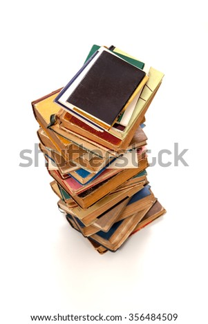 Stack of old books with black covered book on top over white - stock photo