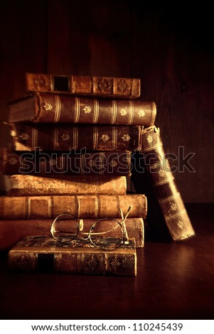 Stack of old books with reading glasses on desk - stock photo