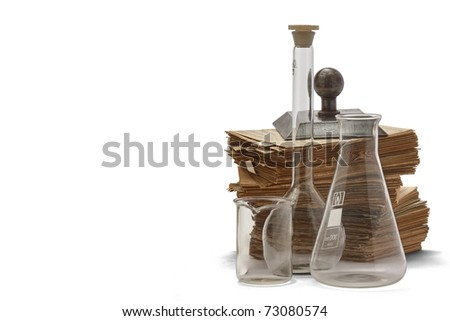 Stack of old catalogue cards with a paper-weight behind transparent chemical glasses isolated - stock photo