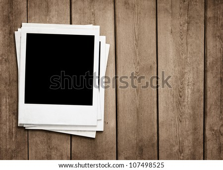Stack of old instant photos at grunge wooden background - stock photo