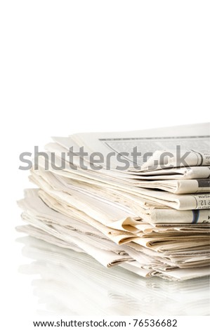 stack of old newspapers with reflection isolated on white