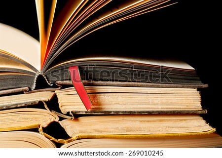 Stack of old open books with a red ribbon place marker. Black background. Close up with copy space. Horizontal - stock photo