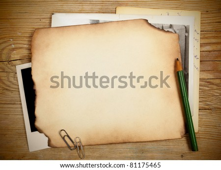 Stack of old papers and photos on a wooden table - stock photo