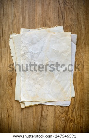 Stack of old papers on a wooden table with vignette - stock photo