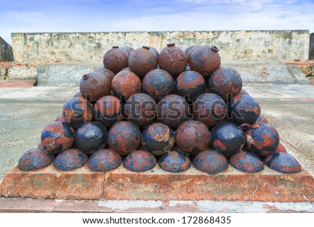 stack of old rusty colonial cannon balls on historic military fort walls - stock photo