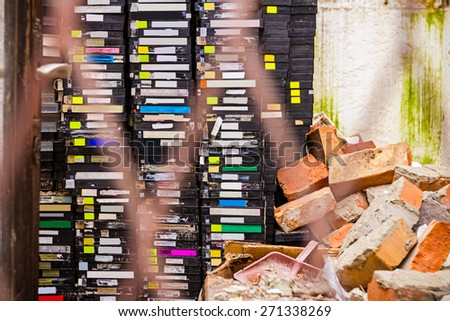Stack of old VHS video cassettes in ruined video store - stock photo