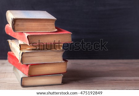 Stack of old vintage books on a rustic wooden table on black school board background. Close up