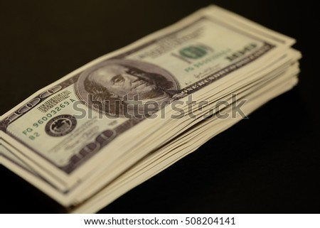 stack of one hundred dollar bills increases on a dark background. bundle of money