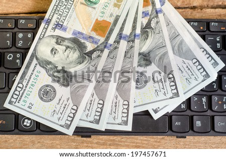 Stack of one hundred dollar bills  on keyboard - stock photo