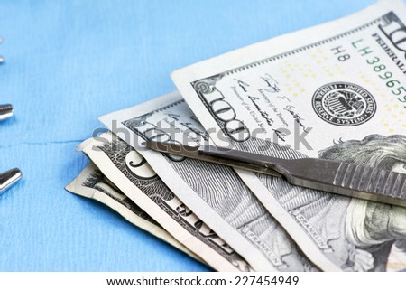Stack of one hundred dollar bills on surgery table.  Concept photo. - stock photo
