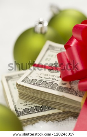 Stack of One Hundred Dollar Bills with Red Bow Near Green Christmas Ornaments on Snow Flakes. - stock photo