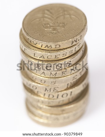 Stack of one pound coins showing latin words on edges.
