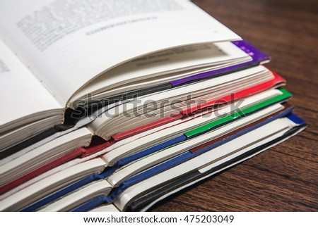 Stack of open books on wooden table, closeup shot