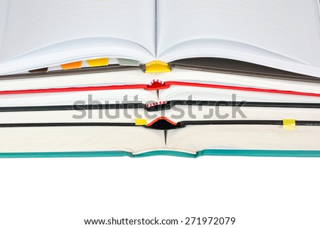 Stack of open books with notebook on top isolated on white background - stock photo