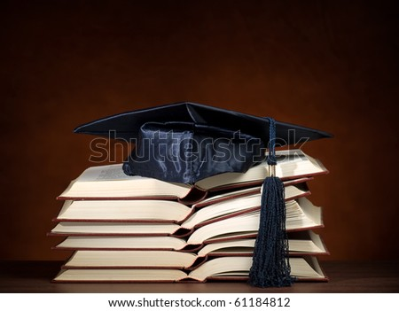 Stack of opened books and graduation cap, for various education,graduation or knowledge themes - stock photo