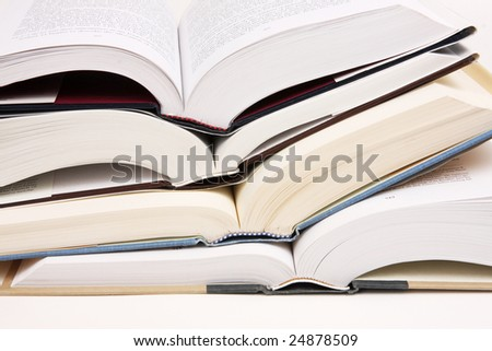 Stack of opened text books on a white background.