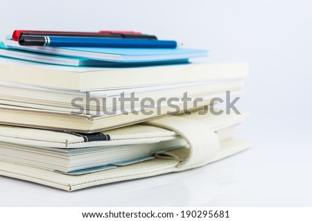 stack of organizer, notebooks, pen and pencil on white background - stock photo