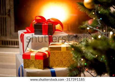 Stack of packed gift boxes under Christmas tree at fireplace - stock photo