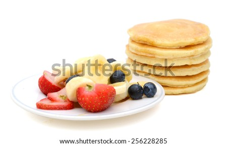 stack of pancakes and plate of fresh fruits isolated on white  - stock photo