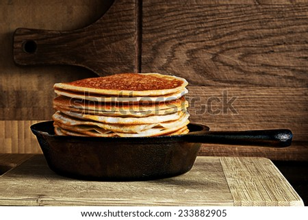 stack of pancakes in a cast iron skillet on a wooden board - stock photo
