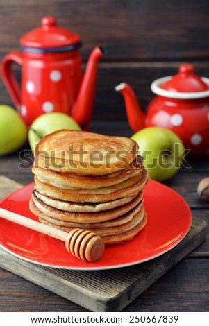 Stack of pancakes on plate with vintage teapots and fresh apples on wooden background - stock photo