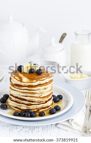Stack of Pancakes served with fresh Blueberries and Maple Syrup on a breakfast table - stock photo