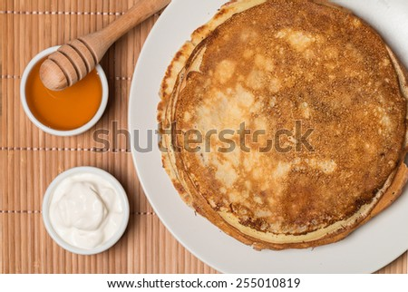 Stack of pancakes sour cream and honey top view - stock photo