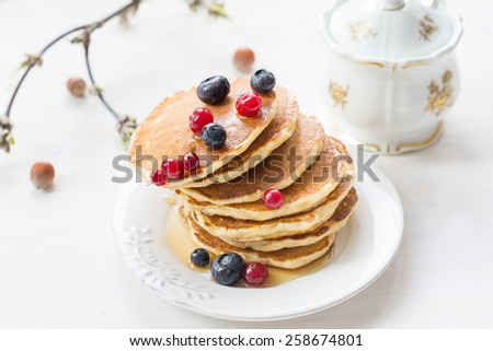 Stack of pancakes topped with berries and maple syrup on white plate on white table - stock photo