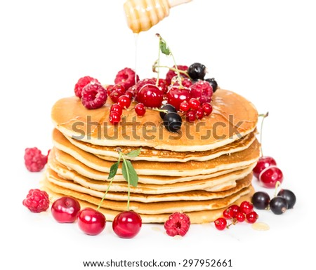 Stack of pancakes with berries and honey isolated on white background