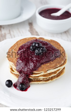 stack of pancakes with black currant jam on a plate - stock photo
