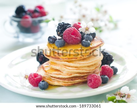 Stack of pancakes with fresh berry and maple syrup, selective focus  - stock photo