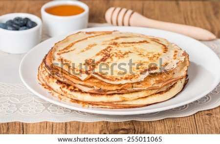 Stack of pancakes with fresh blueberry and honey on wooden table