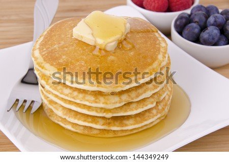 Stack of pancakes with fruits on background. Top view.