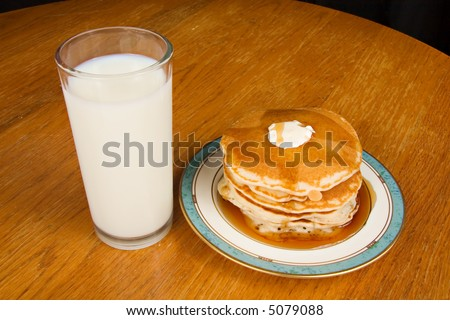 Stack of pancakes with glass of milk - stock photo