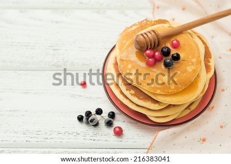 Stack of pancakes with honey and berries on wooden background. - stock photo