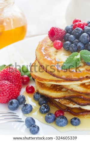 Stack of Pancakes with honey and fresh berries on white plate close up