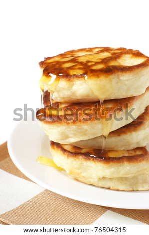Stack of pancakes with honey on white plate.