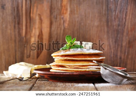 Stack of pancakes with mint and butter on rustic wooden background - stock photo