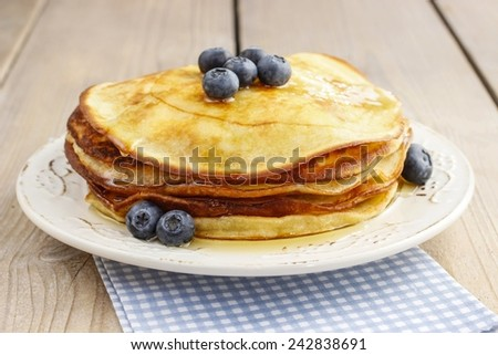 Stack of pancakes with syrup and blueberries - stock photo