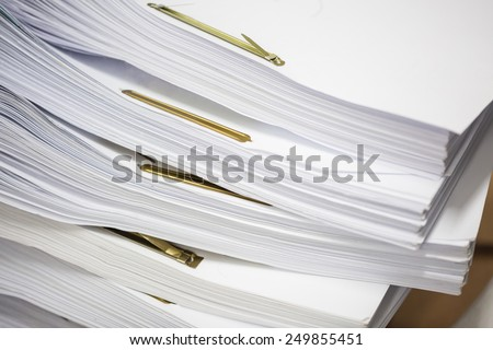 Stack of paper files with golden clips - stock photo