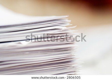 Stack of papers, focus in corner of stack - stock photo