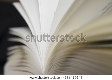 Stack of papers in an open book with text and shallow depth of field, black background - stock photo