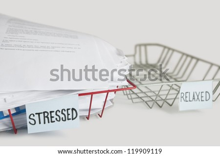 Stack of paperwork in stressed tray with empty relaxed platter over white background - stock photo