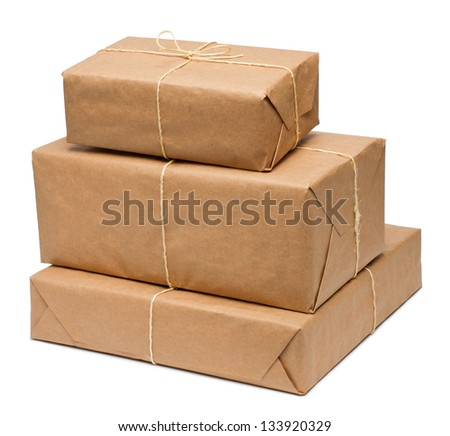 Stack of parcel wrapped in brown paper and tied with rough twine - stock photo