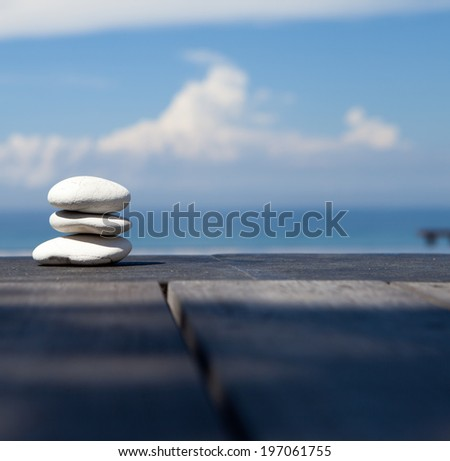Stack of pebble stones at the beach on a wooden surface - stock photo